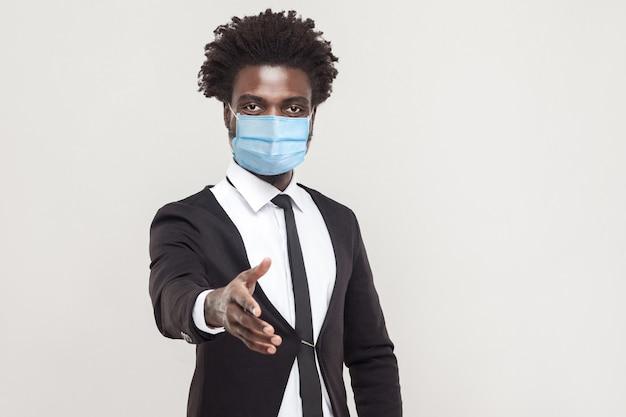 いらっしゃいませ。サージカルマスクが立って、助け、サポート、または挨拶のために手を差し伸べる黒いスーツを着ている親切な若いハンサムな労働者の男の肖像画。灰色の背景に分離された屋内スタジオショット
