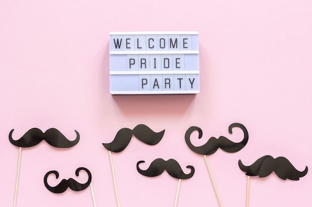 Welcome pride party, paper mustache props on pink background.