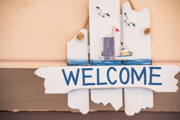 Welcome sign hanging on rustic wooden background.