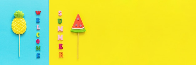Welcome summer colorful text, pineapple and watermelon lollipops on stick on blue yellow background. concept vacation