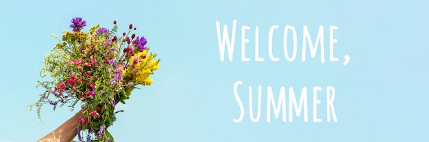 Welcome summer text. female hand holds bright colorful bouquet of wild flowers against blue sky. hello summer concept