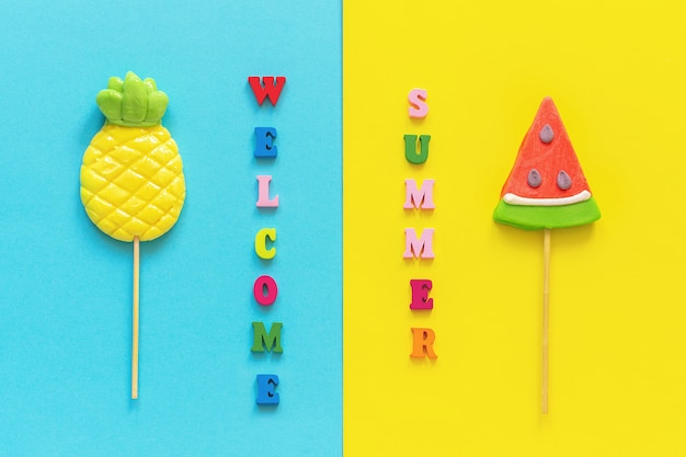 Welcome summer text, pineapple and watermelon lollipops on blue yellow background.