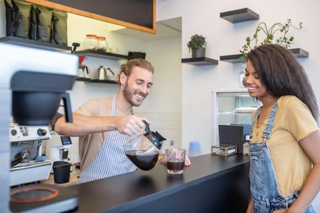 커피에 오신 것을 환영합니다. 카운터 뒤에 유리에 커피를 붓고 즐거운 혼혈 여자를 기다리는 자비로운 웃는 남자