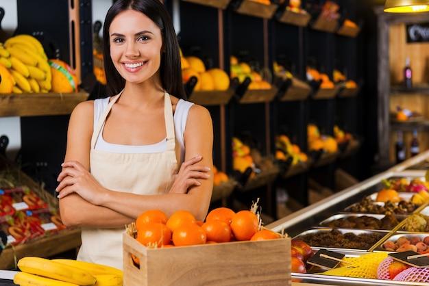 フルーツパラダイスへようこそ!さまざまな果物を背景に食料品店に立っている間、腕を組んで笑顔を保つエプロンの美しい若い女性