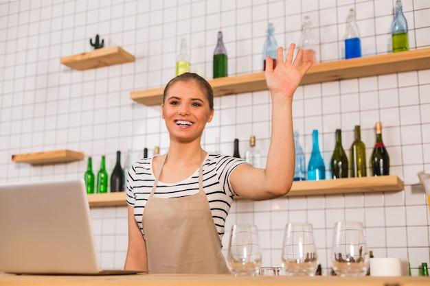 私たちのカフェへようこそ。幸せなフレンドリーなポジティブな女性が笑顔で顧客に挨拶しながら手を振る