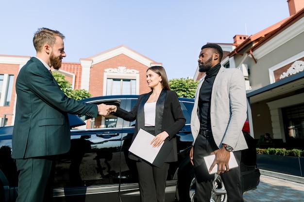 私たちのチームへようこそ。屋外の車の近くに立って3人の若い多民族のビジネス人々。新しい同僚の男と握手幸せな若い女、タブレットを保持しているアフリカ人が近くに立つ