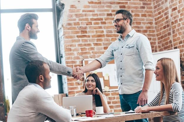 Добро пожаловать в нашу команду! двое мужчин пожимают друг другу руки и улыбаются, пока их коллеги сидят за столом в офисе