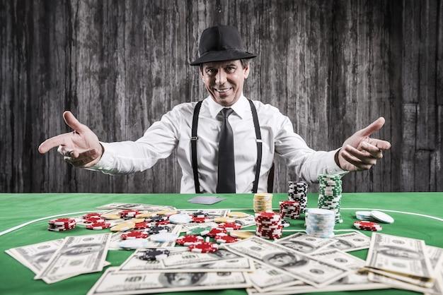 게임에 오신 것을 환영합니다! 셔츠와 멜빵을 입은 웃고 있는 노인이 포커 테이블에 앉아 그 근처에 누워 있는 돈과 도박 칩으로 몸짓