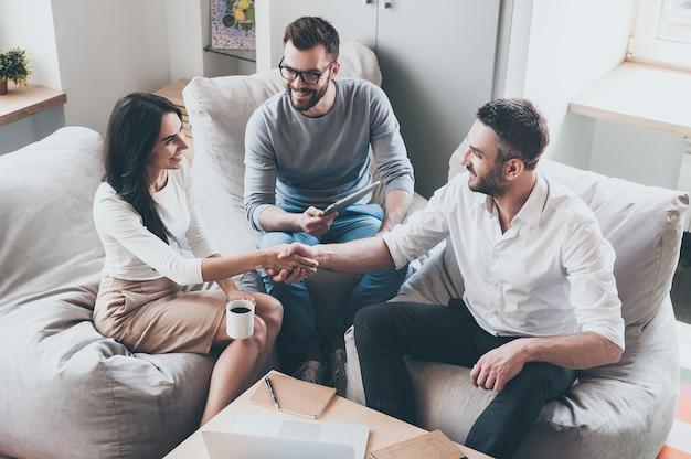 팀에 오신 것을 환영합니다! 남자와 여자가 악수하는 동안 책상에 함께 앉아 세 젊은 쾌활한 사업가의 상위 뷰