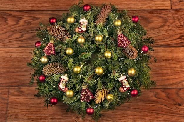 크리스마스 황금 공과 화환으로 장식 된 가문비 나무 가지의 전통적인 화환을 환영합니다.