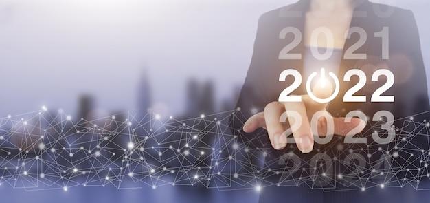 2022년을 환영합니다. 비즈니스 새 해 카드 개념입니다. 손으로 터치하는 디지털 화면 홀로그램 2022는 도시의 불빛이 배경을 흐리게 합니다. 비즈니스 새 해 카드 개념입니다.