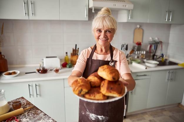Приветствуя пожилую женщину, позирующую с кучей свежеиспеченной выпечки