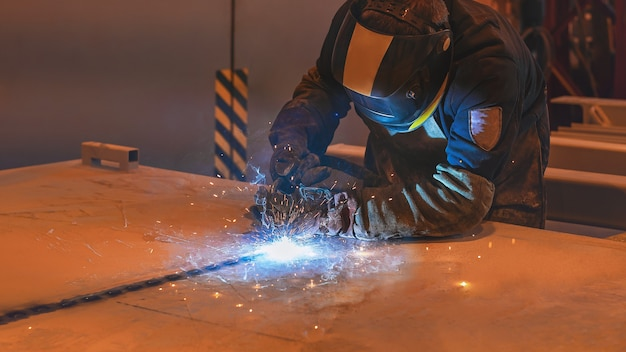 A welder in a black and yellow mask performs work with a migmag welding machine welding works