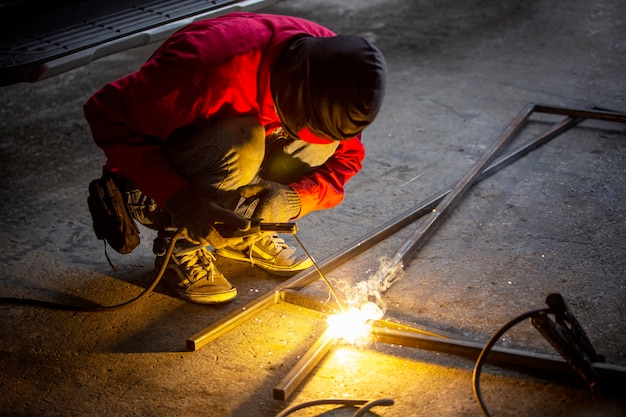 溶接工は、工業工場で溶接プロセスを行い、フレームに器具を入れて手渡します。