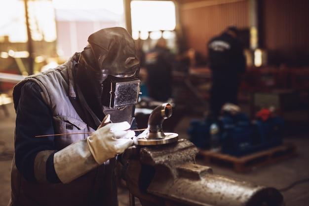 Сварщик в защитной форме и маске сварки металлической трубы на промышленном столе во время искры.