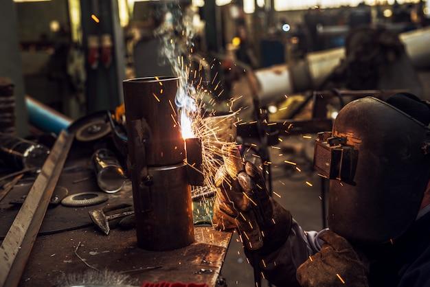 Сварщик в защитной форме сваривает металлическую трубу в своей мастерской, а перед ним летят искры.
