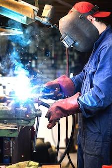 Welder is welding metal part in garage. with protective mask, industrial steel welder