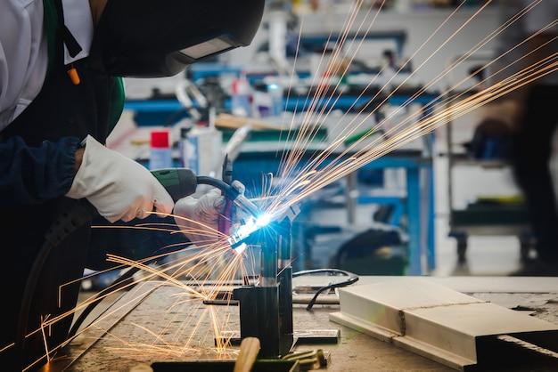 Сварщик сваривает металлические детали на автосборочном заводе и отрабатывает навыки сварщика на промышленных предприятиях.