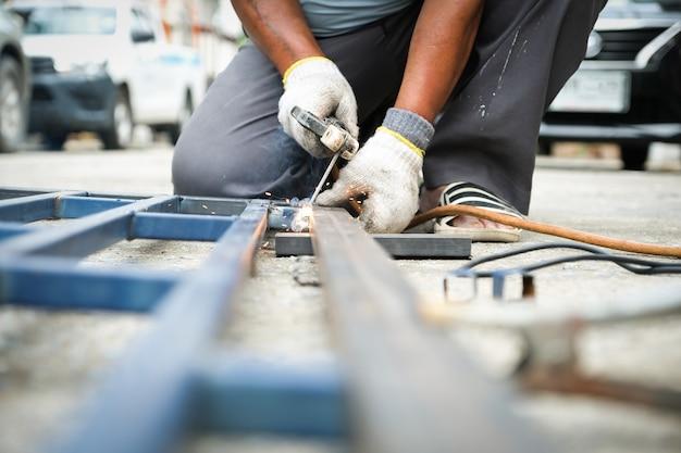 Сварщик сваривает стальную конструкцию, чтобы добавить к дому. Premium Фотографии