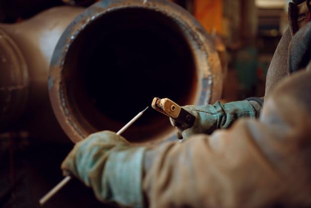 Сварщик готовит электроды к сварке на заводе