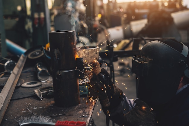 Welder in protective uniform and mask welding metal pipe on the industrial table while sparks flying.