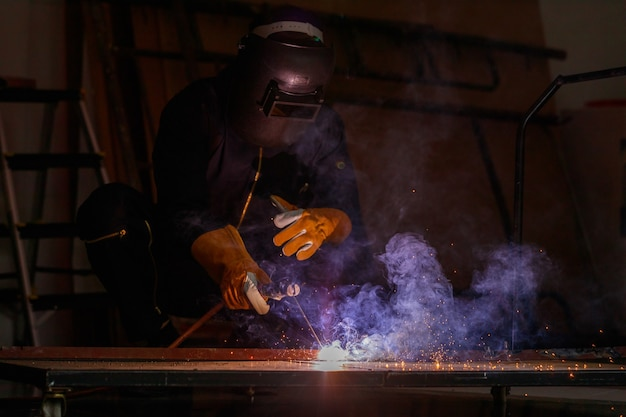 Welder sitting in factory welding steel together to make it stronger. work produces bright sparks have smoke, effect form light plus smoke make it looks beautiful purple light.