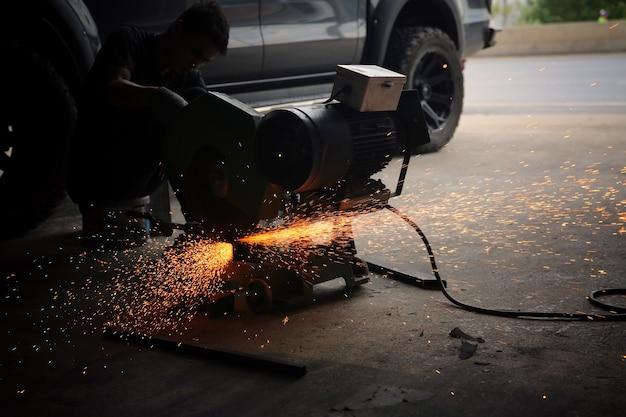 溶接機は、火花のある工場で鋼の砥石を使用し、産業ワークショップでの溶接プロセス、フレーム内の器具を備えた手。