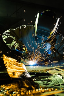 A welder wearing a mask while working on detail