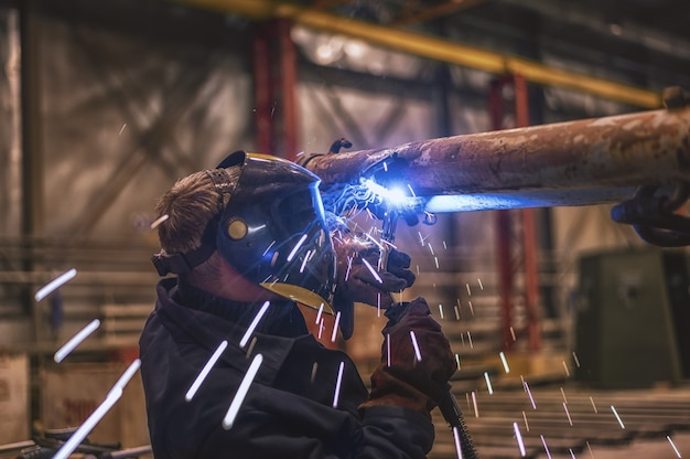 A welder wearing a protective mask performs work using a migmag welding machine