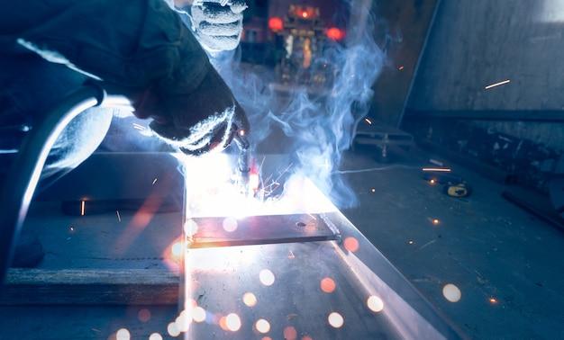 Welder welding metal with argon arc welding machine and has welding sparks and smoke man wear glove
