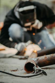 Сварщик сваривает металлическую трубную конструкцию