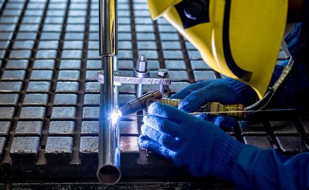 Сварщик работает на сталелитейном заводе с помощью аргонной сварки.