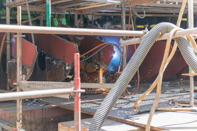 Сварщик работает на судоремонтном заводе - горячие работы