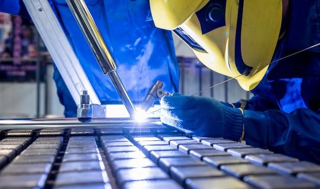 Welder working in a steel factory with argon welding.