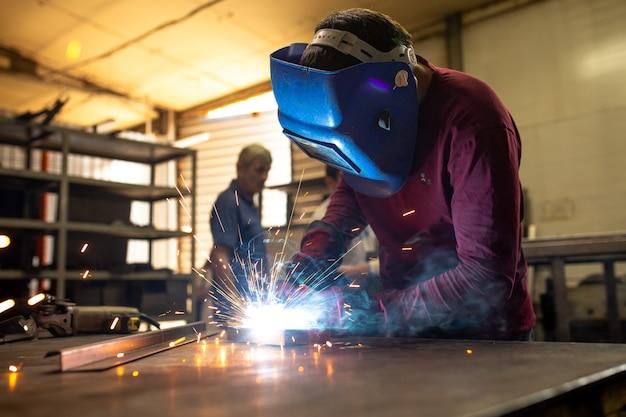Сварщик работает на металлической поверхности