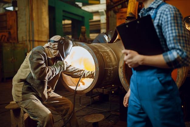 Сварщик работает на заводе