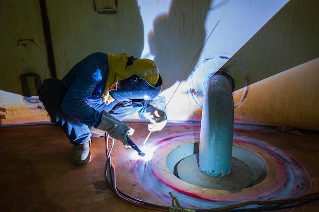 Сварочная дуга, работающий на аргоне, отремонтированный мужчина, является частью конструкции масляного резервуара отстойника коробки внутри ограниченного пространства