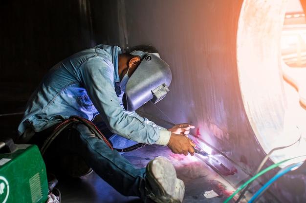 Сварочная дуга аргона рабочий мужчина отремонтировал металл сварочные искры промышленное строительство резервуар для масла в замкнутых пространствах.