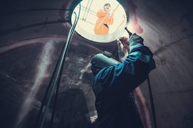Сварочная дуга аргоновый рабочий мужчина отремонтировал металл сварочные искры промышленное строительство резервуар часть люка нержавеющее масло внутри замкнутых пространств есть сторож снаружи.