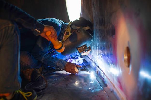 Сварочная дуга аргона рабочий мужчина отремонтировал металл сварочные искры резервуар промышленного строительства из нержавеющей стали в замкнутых пространствах.