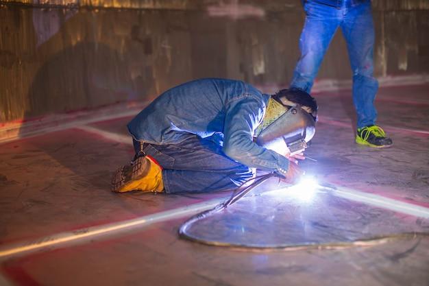 溶接アークアルゴン労働者の男性の修理された金属は、限られたスペース内で火花産業建設タンクのステンレス油を溶接しています。