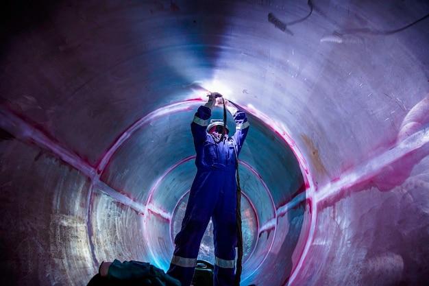 용접 아크 아르곤 작업자 남성 수리 금속은 제한된 공간 내에서 산업 건설 탱크 스테인리스 오일을 용접하고 있습니다.
