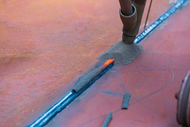 Welding hard surfacing of tank bottom plate steel roll by slag submerged arc welding process.