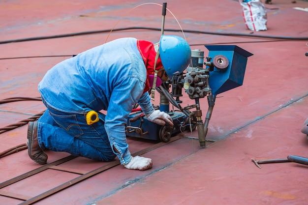 Сварочный рабочий контролирует наплавку стального валка днища резервуара методом дуговой сварки под флюсом.