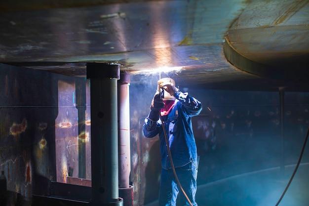 Металлическая дуга сварщика мужского пола является частью конструкции трубопровода сопла резервуара машиностроения резервуара для хранения нефти и газа в замкнутых пространствах.