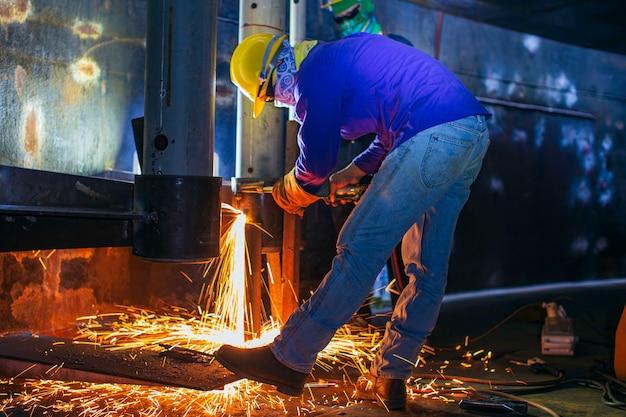 男性労働者の金属アークの溶接は、限られたスペース内の機械タンクノズルパイプライン建設石油およびガス貯蔵タンクの一部です。