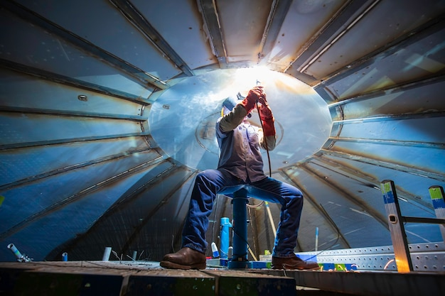 男性労働者の金属アークの溶接は、限られたスペース内の屋根タンク建設石油およびガス貯蔵タンクの一部です。
