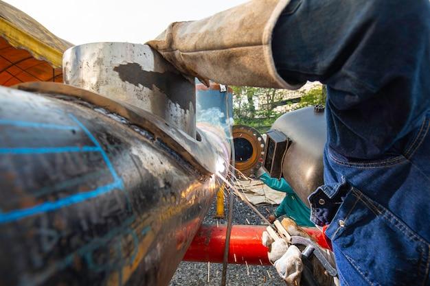 용접 남성 작업자 금속은 기계 노즐 파이프라인 건설 석유 및 가스의 일부입니다.