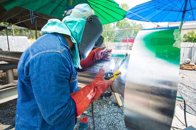 용접 남성 작업자 금속은 기계 노즐 파이프라인 스테인리스 스틸 건설 석유 및 가스의 일부입니다.