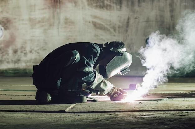 男性労働者の金属の溶接は、限られたスペース内の機械タンクプレート底部建設石油およびガス貯蔵タンクの一部です。